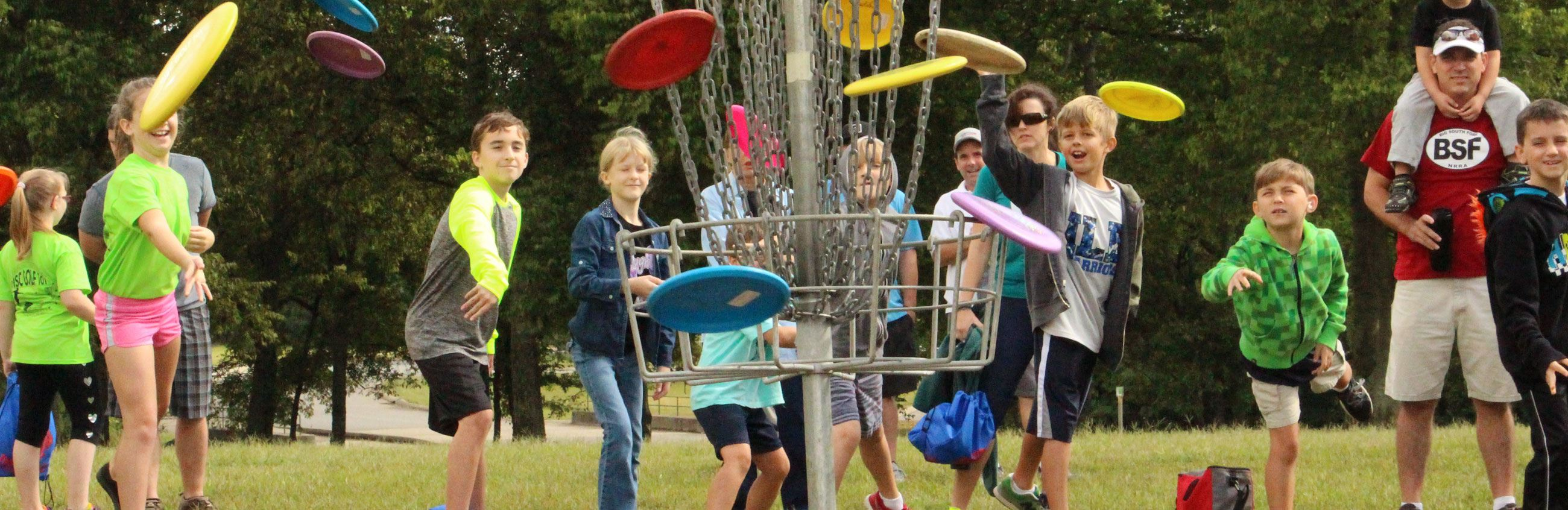Multiple kids shooting frisbee golf