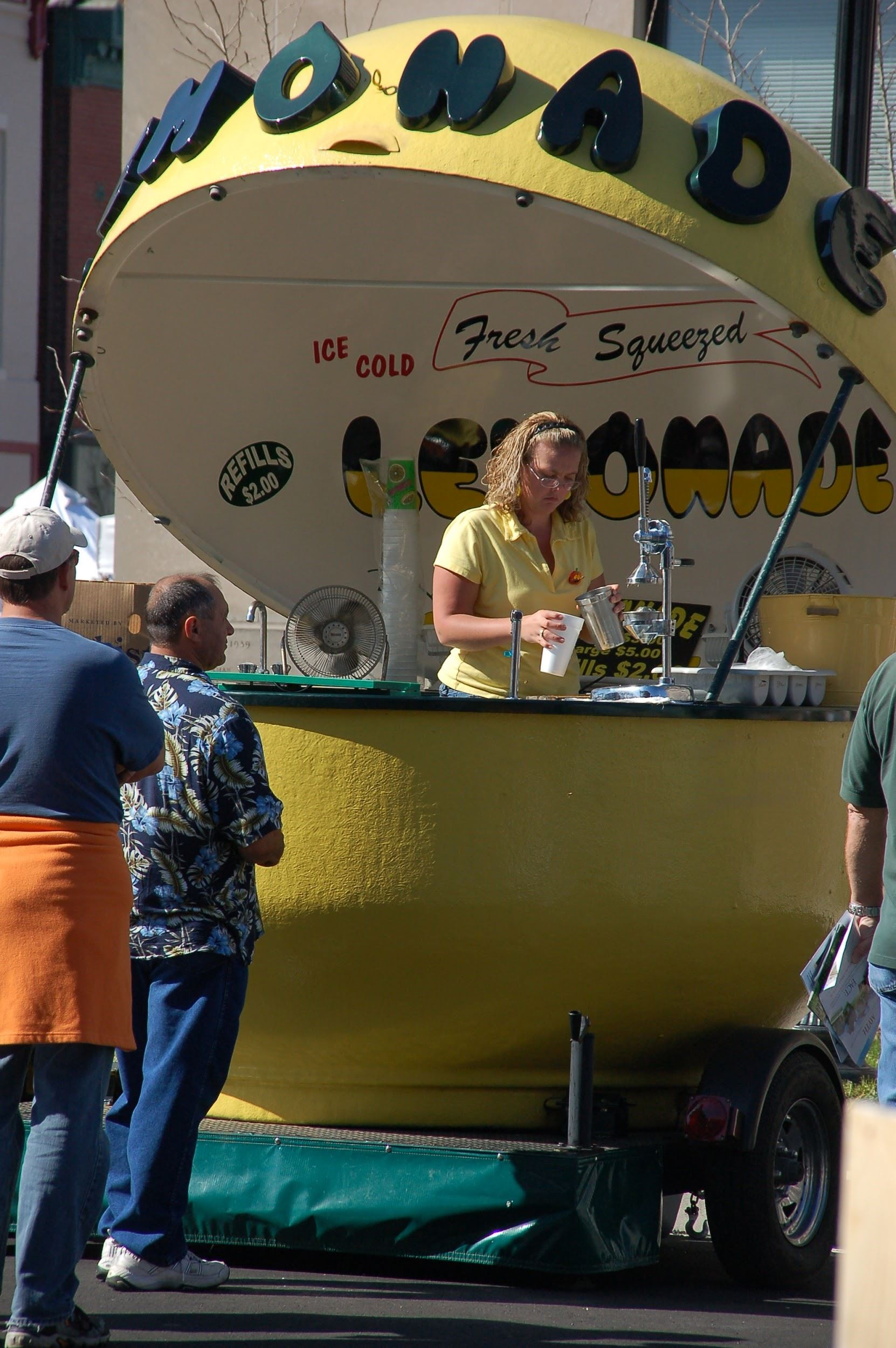 Woman serving lemonade in stand shaped like giant lemon