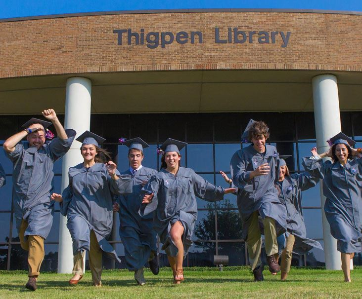 Graduates running in front of Thigpen Library