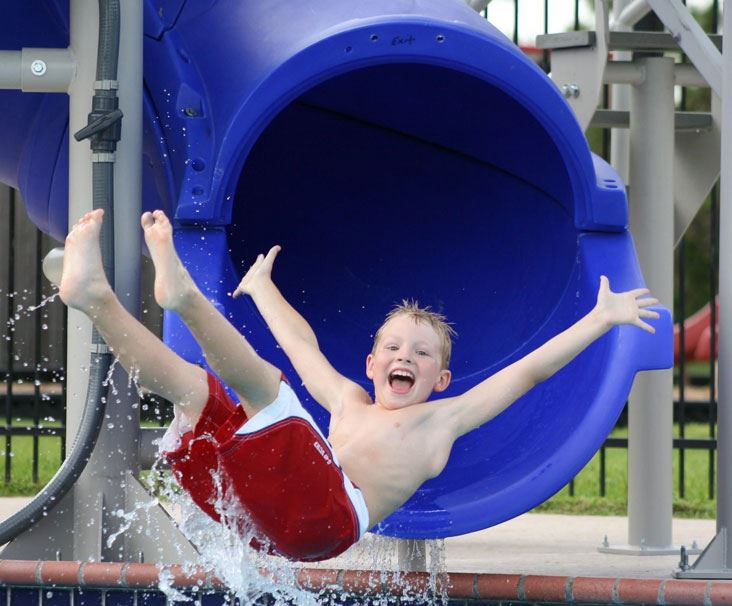 Boy splashing out of blue water slide