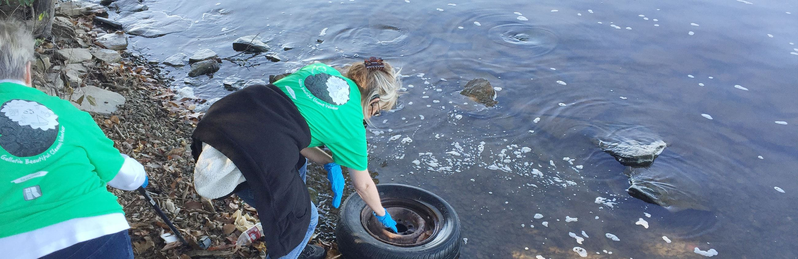 Woman picking up tire along shoreline
