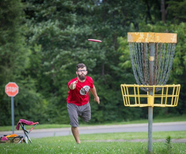 Bearded man in red shirt playing frisbee golf