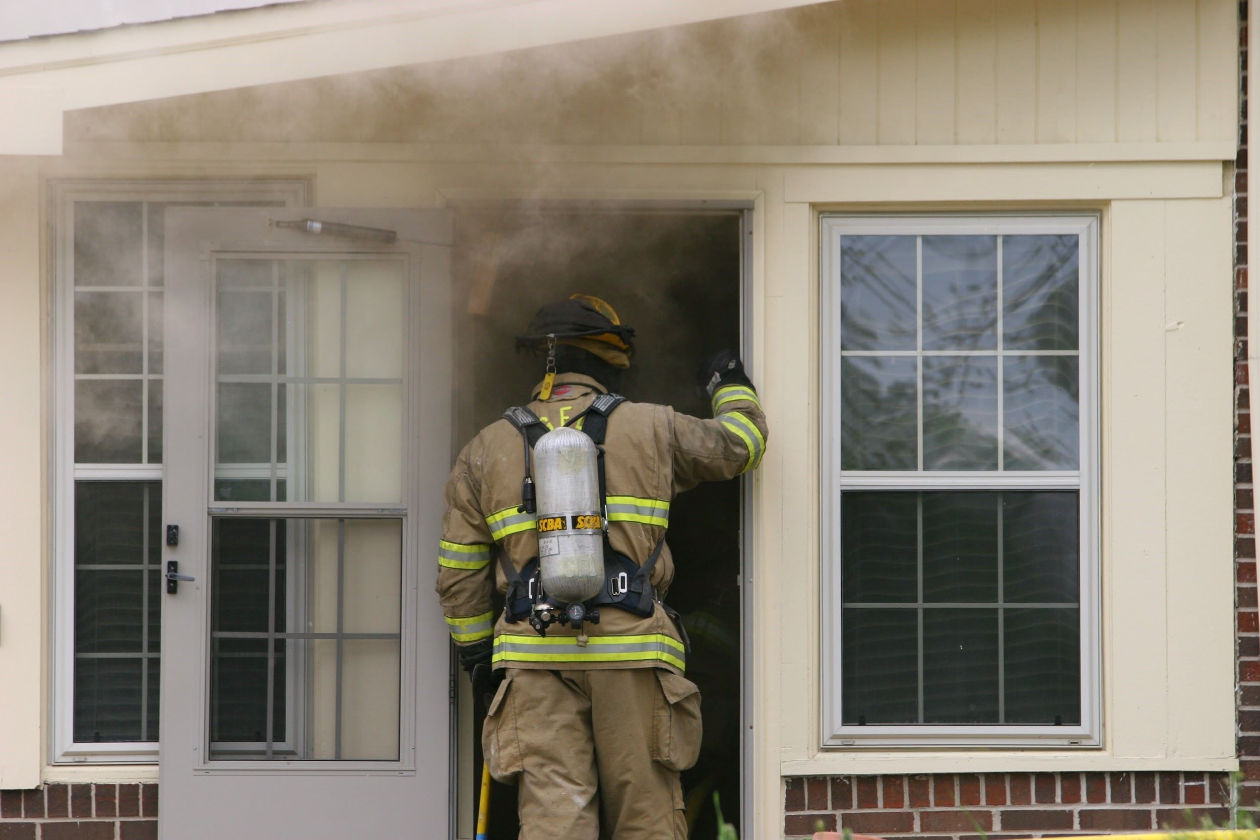 Fireman Entering Home with smoke coming out front door