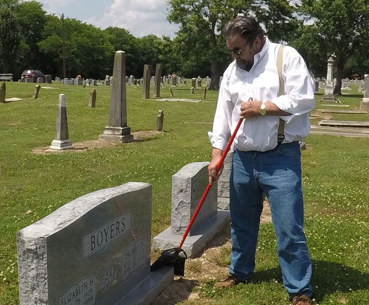 Thomas Boyers cleans headstones at the Historic Gallatin City Cemetery