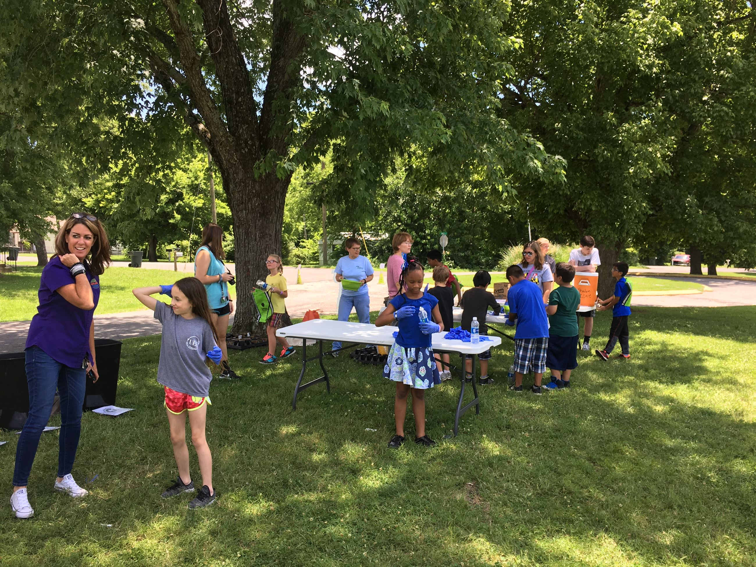 Volunteers interacting With Children outdoors under Trees