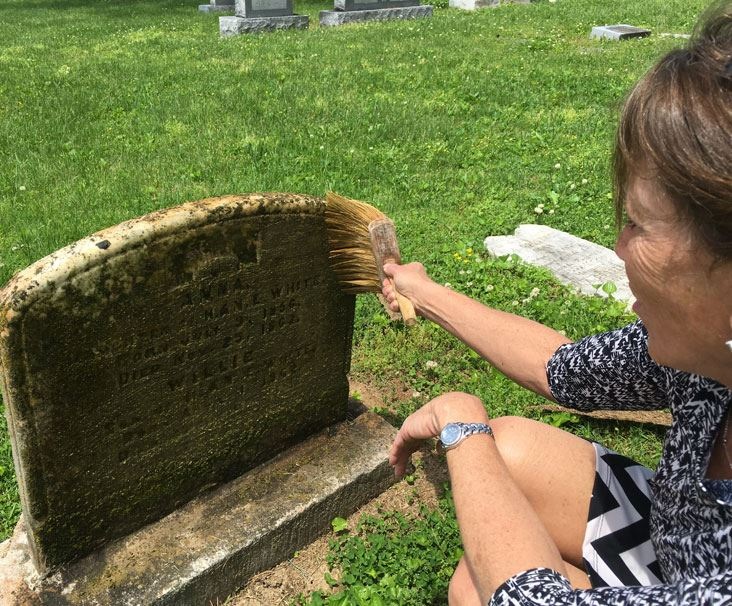 Mayor Brown cleans monument at Gallatin City Cemetery