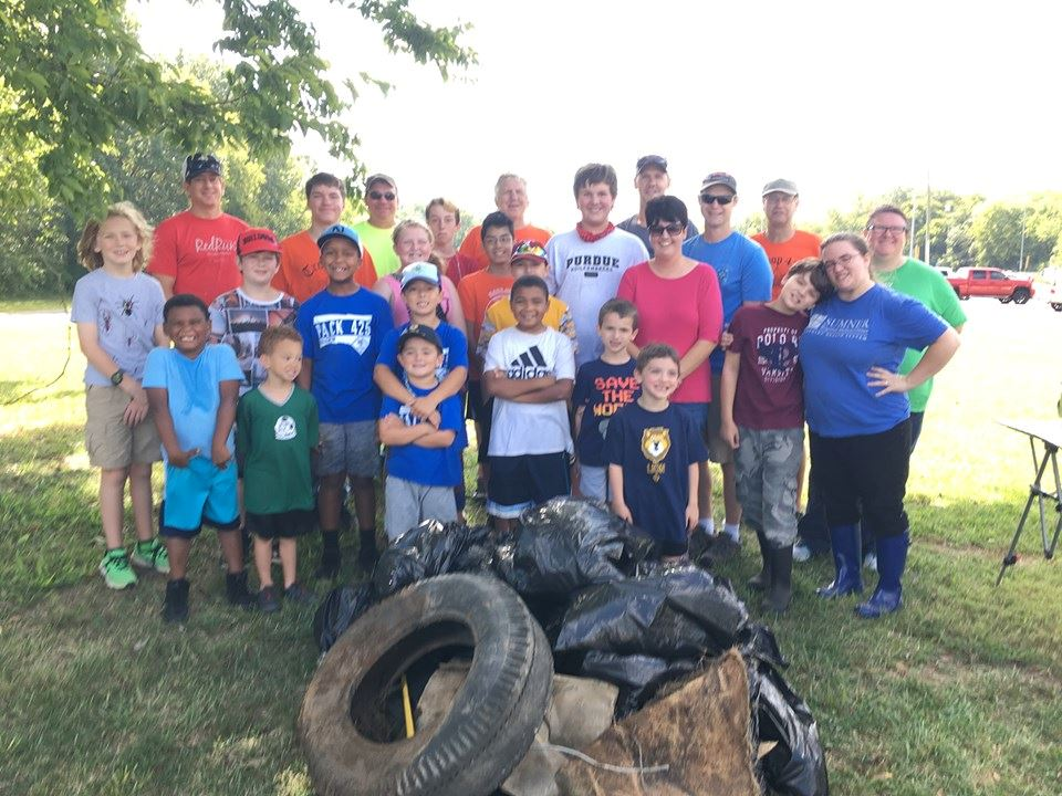 Cub Scout Pack and Leaders behind a pile of trash in the park