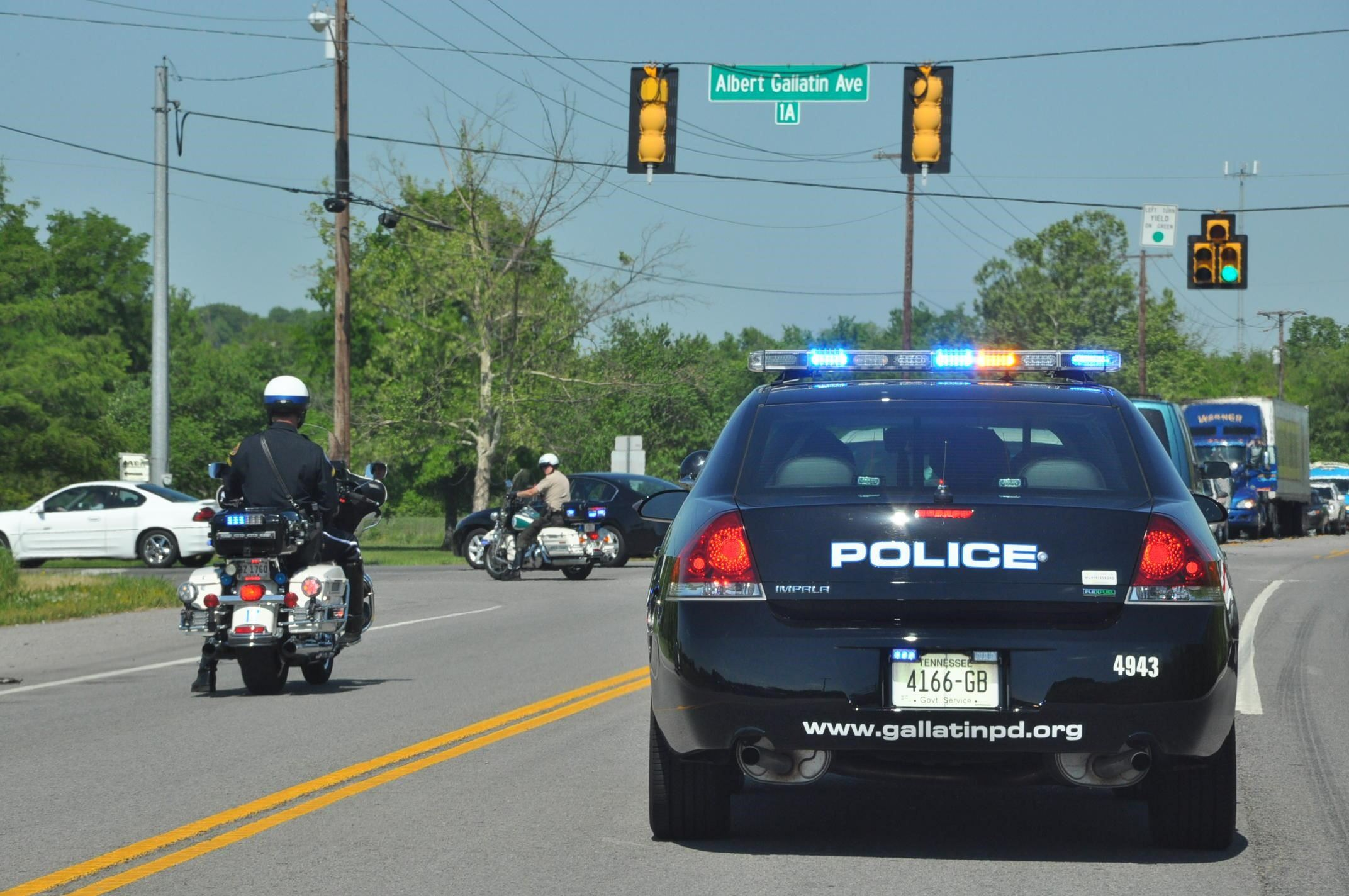 Police cruisers and motorcycles in traffic.