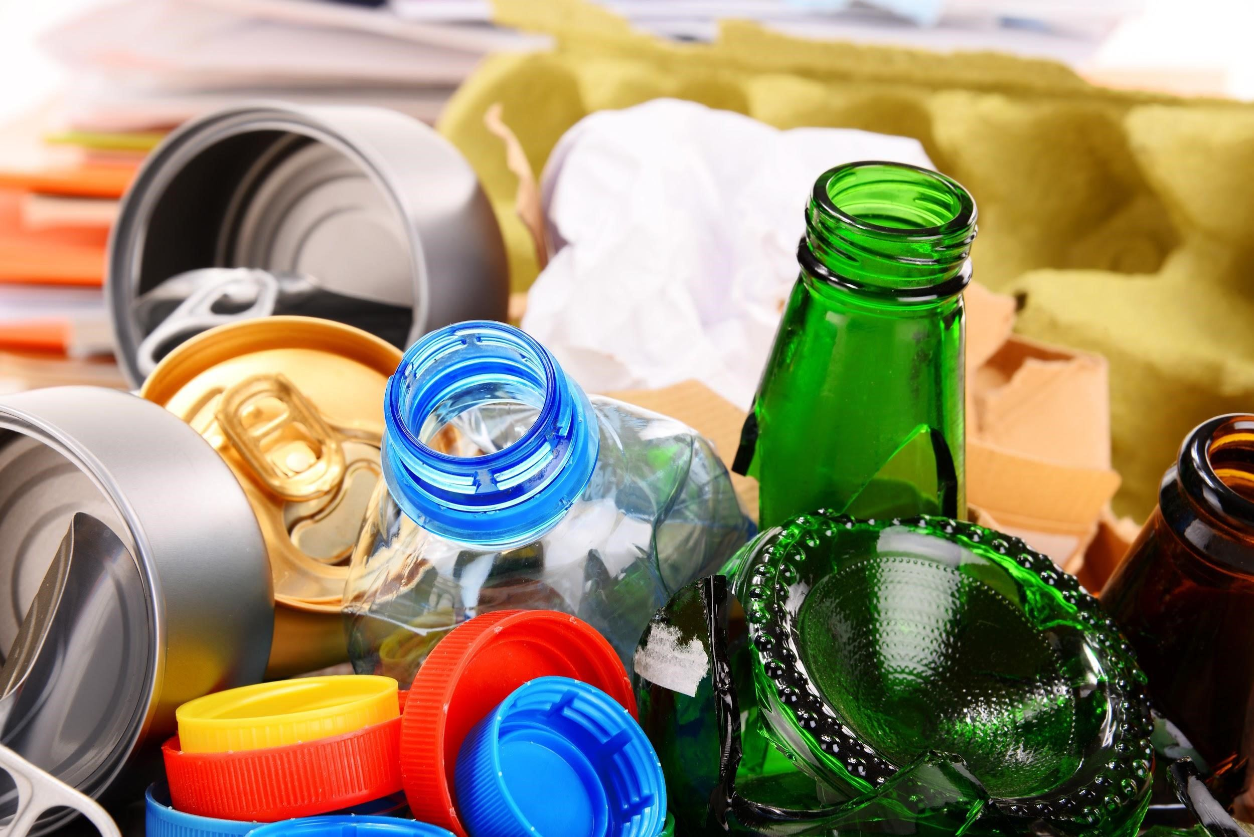 Up close of glass bottles, plastic bottles, cans, and lids
