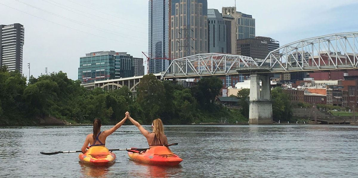 Two girls kayaking the Cumberland near Downtown Nashville