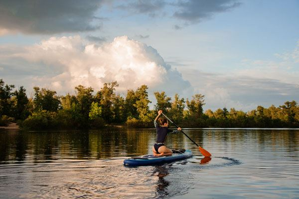 Woman sits on sup board holds paddle and floats on the river