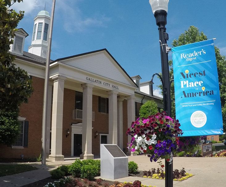 Gallatin City Hall with flowers, blue sky, and Nicest Place in America avenue banner