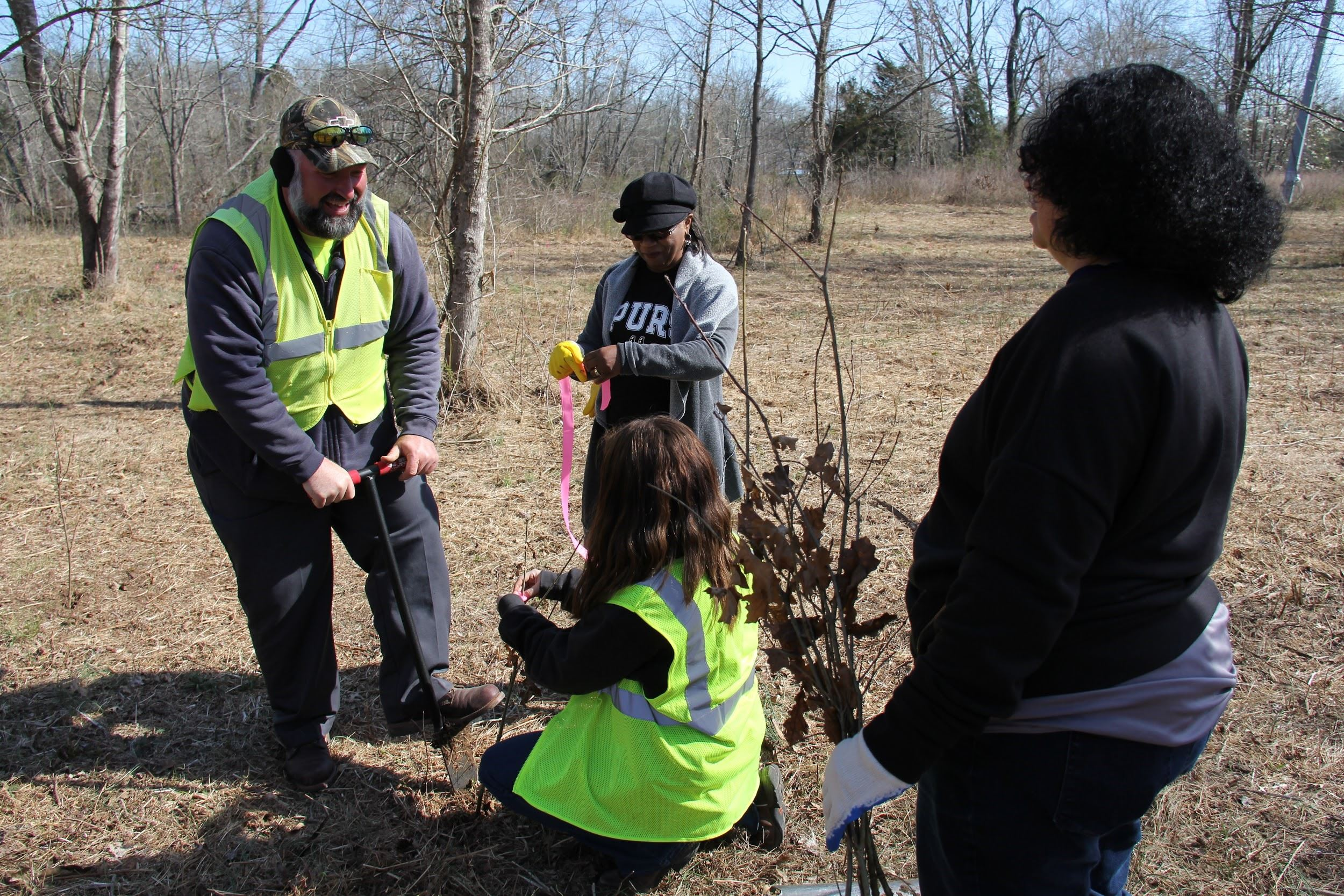 Arbpr Day Tree Planting, four people in woods planting trees