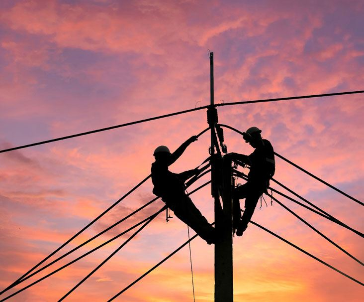 Two power-pole workers with pink sunset background